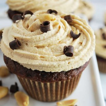 close up of a peanut butter frosting swirled on a cupcake with shaved chocolate on top