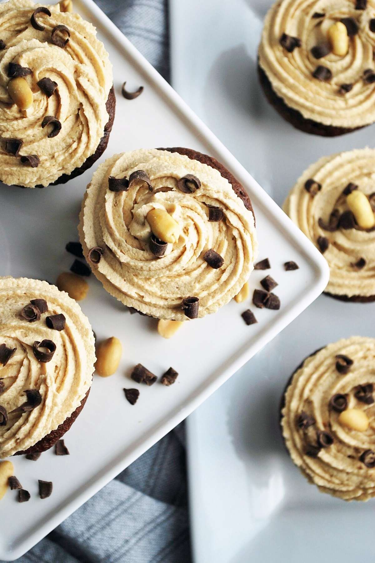 overhead photo looking down on a platter of frosted cupcakes topped with chocolate shavings