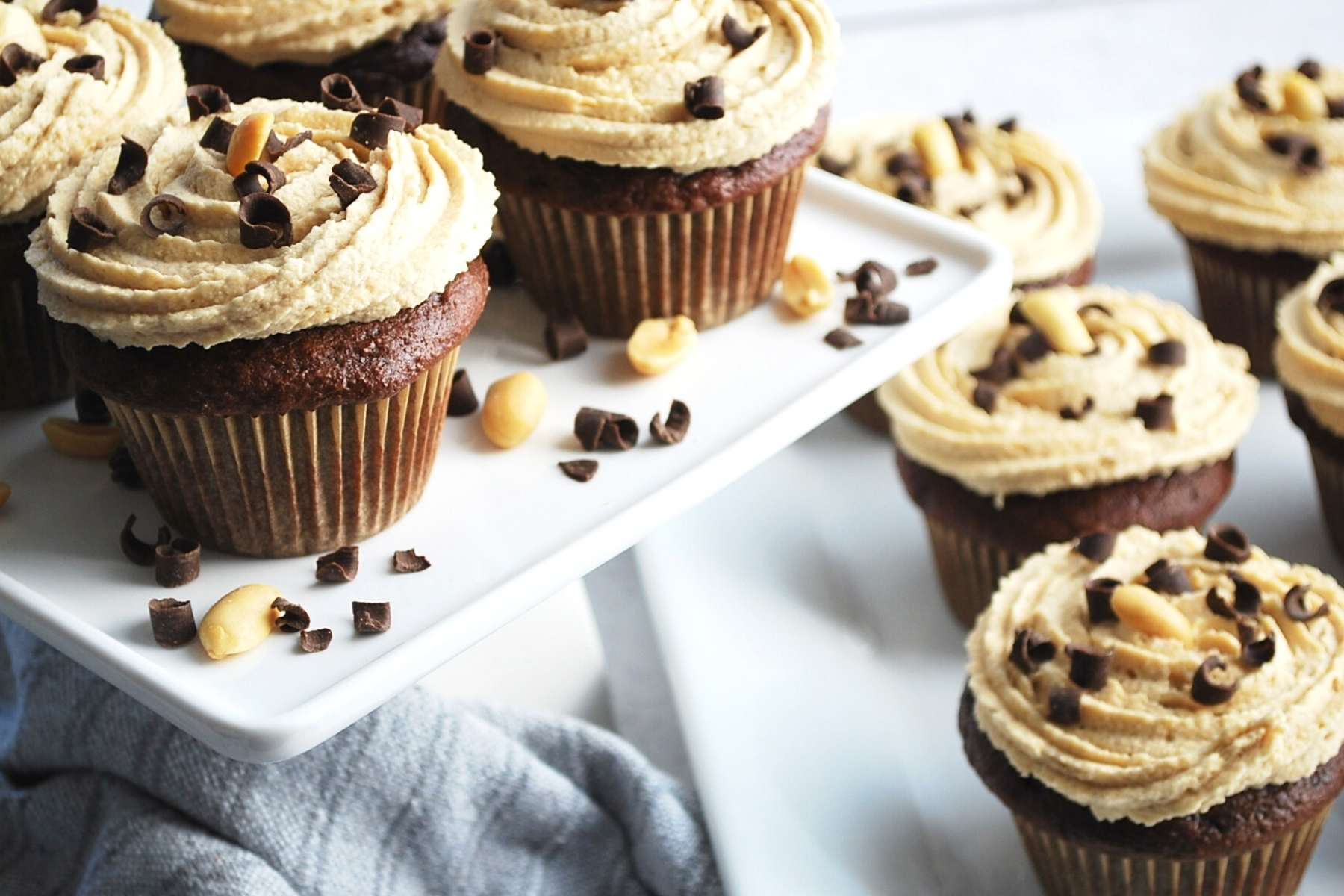 side view of a chocolate cupcakes with peanut butter cream cheese frosting swirled on top