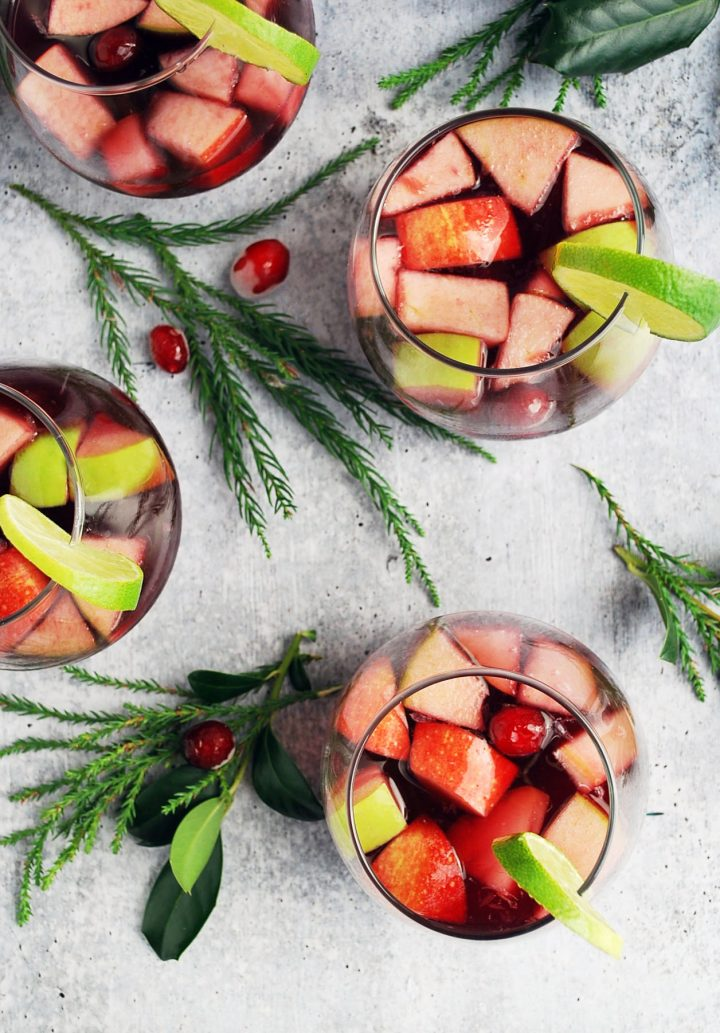 overhead photo of four glasses of Christmas sangria with greenery in background