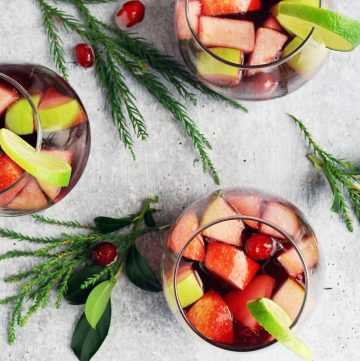 three glasses of sangria with chopped fruit with holly and greenery in background