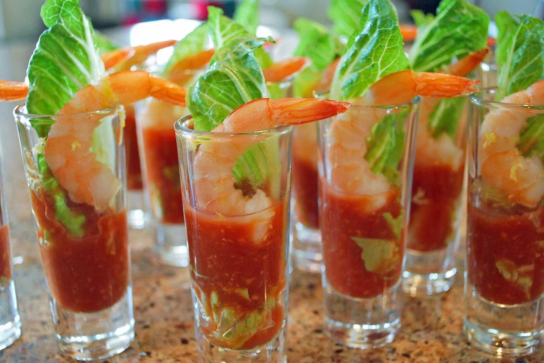 mini glasses filled with cocktail sauce, a shrimp, lettuce leaf, and lemon zest