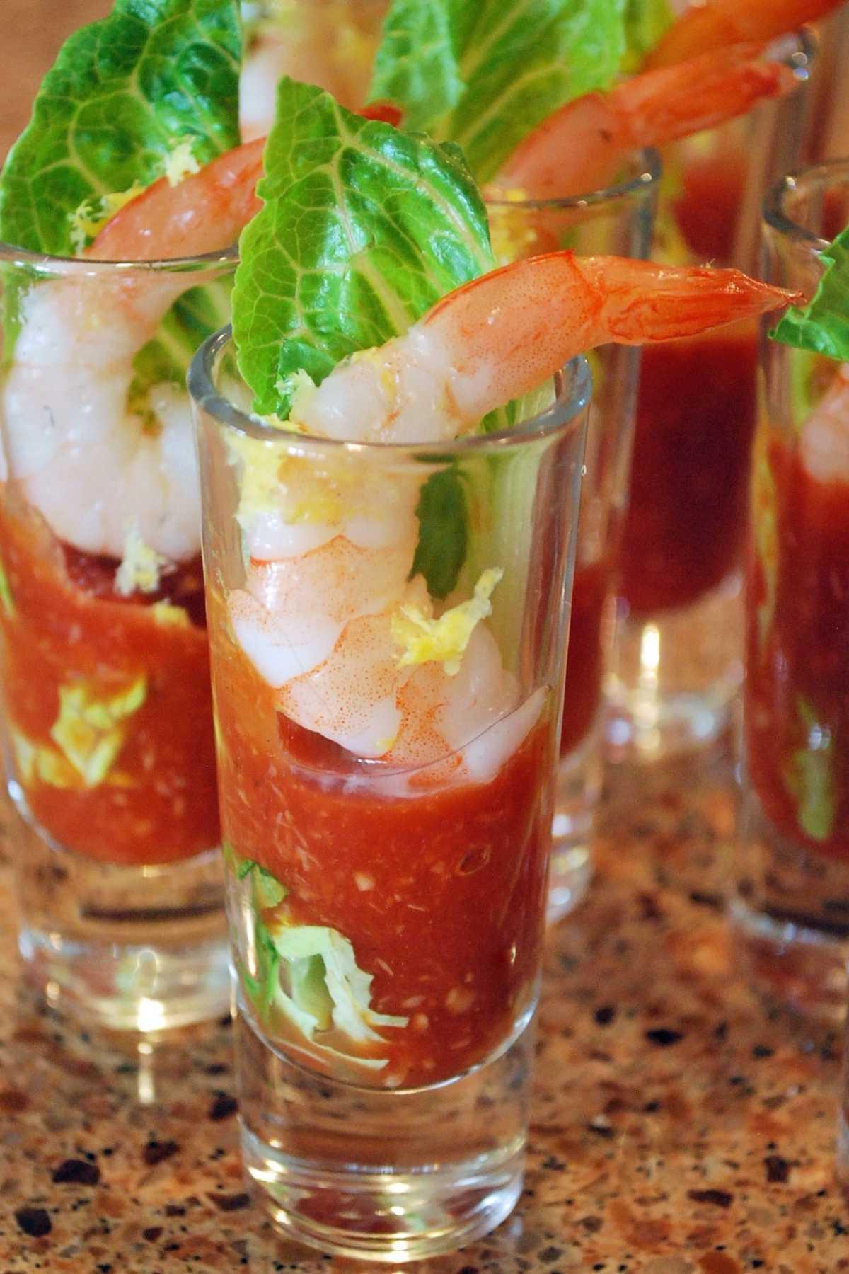 shrimp shooters in mini parfait glasses with romaine, cocktail sauce, and fresh lemon zest