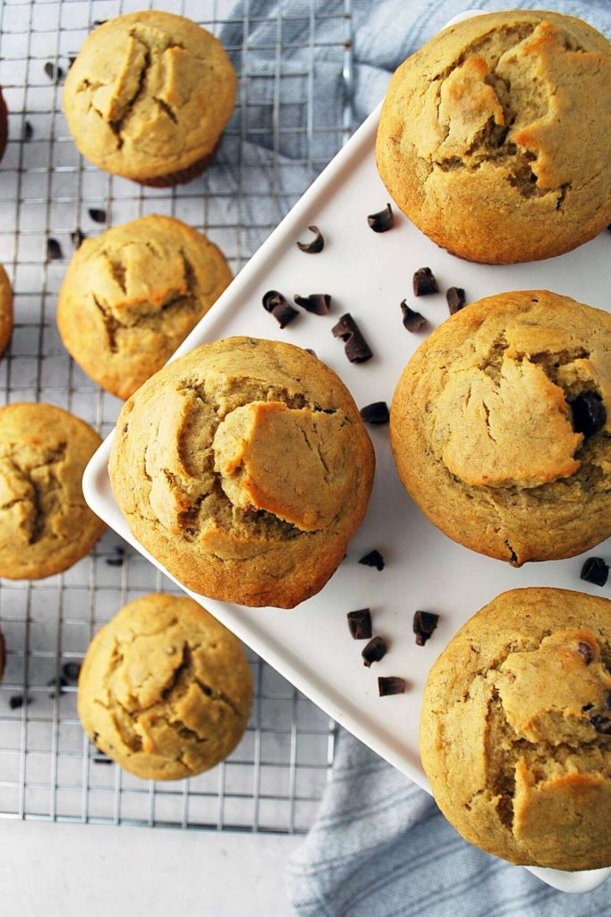 gluten-free banana chocolate chip muffins on a platter with a baking rack of muffins underneath
