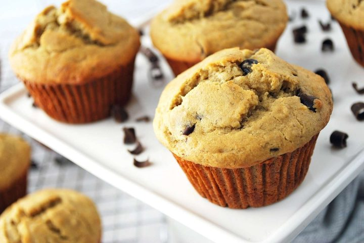gluten-free banana chocolate chip muffins on a platter with chocolate shavings