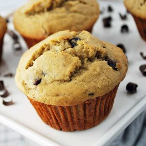close up photo of a banana muffin with chocolate chips on a platter