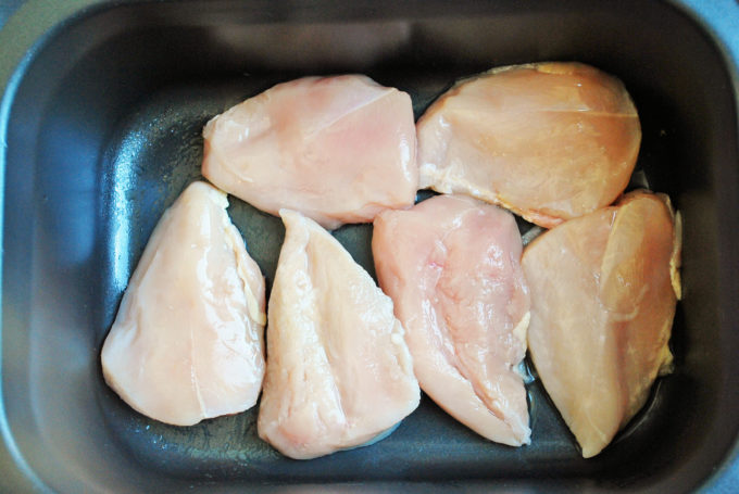 Raw chicken breasts in the bottom of a slow cooker