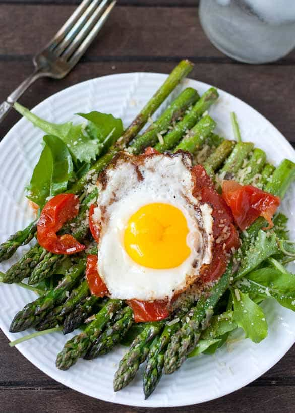 warm salad with asparagus and tomatoes, topped with a fried egg