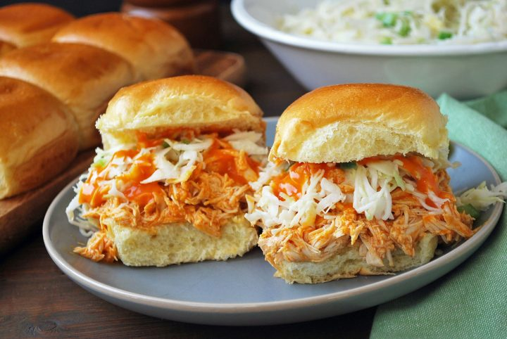 buffalo sliders plated with slaw and hot sauce with rolls in background