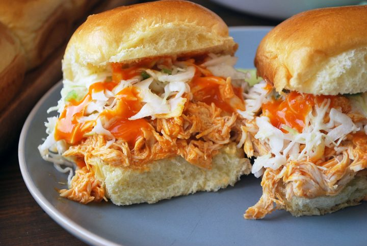 close up photo of sliders with slaw and wing sauce