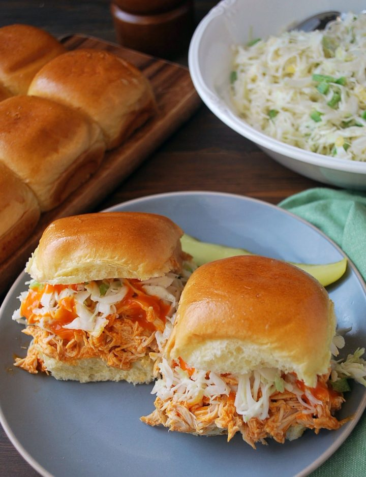 sliders on a plate with pickle with slaw and rolls