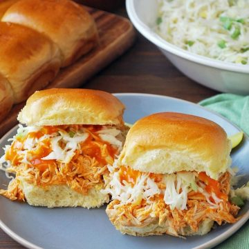 two buffalo sliders on a plate with slaw and rolls in background