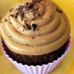 a chocolate pumpkin cupcake with chocolate shavings on top