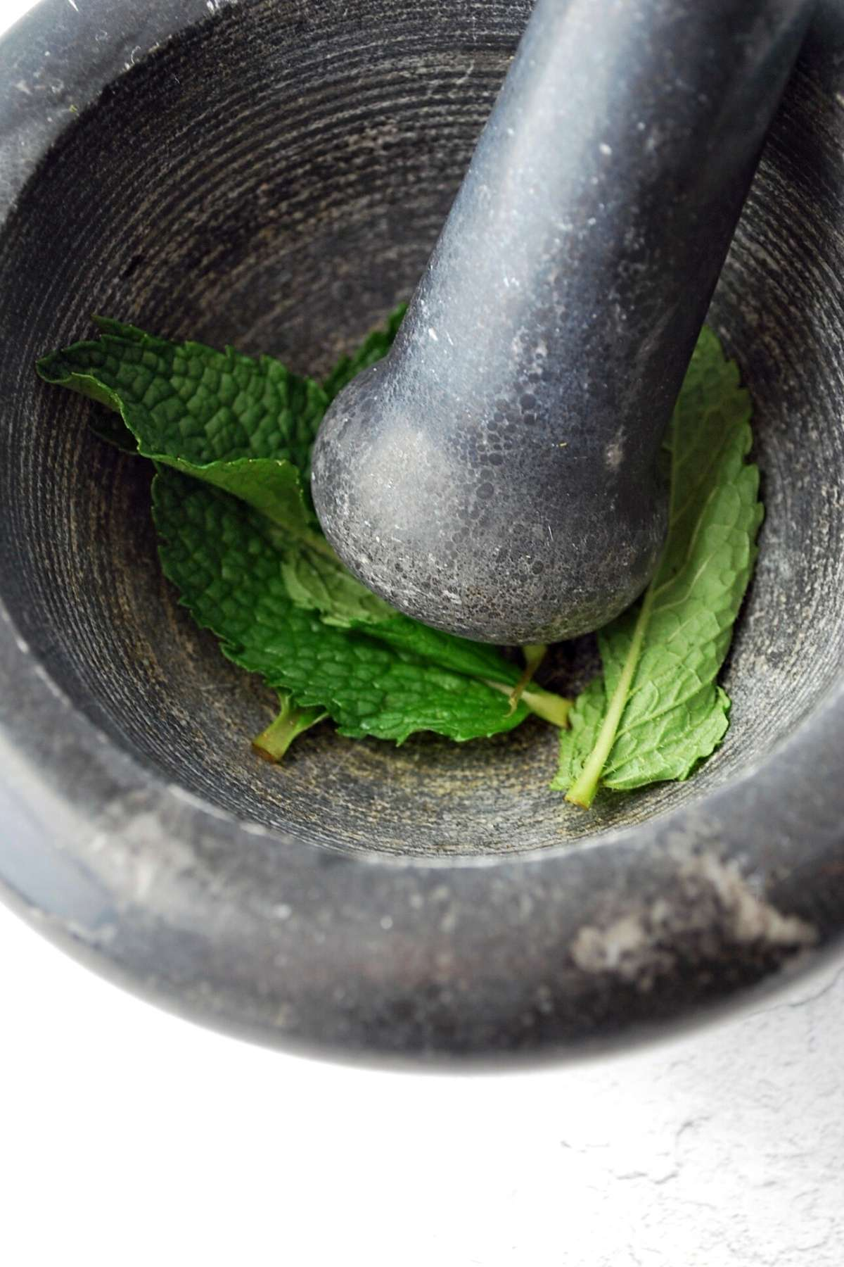 muddling mint in a mortar and pestle