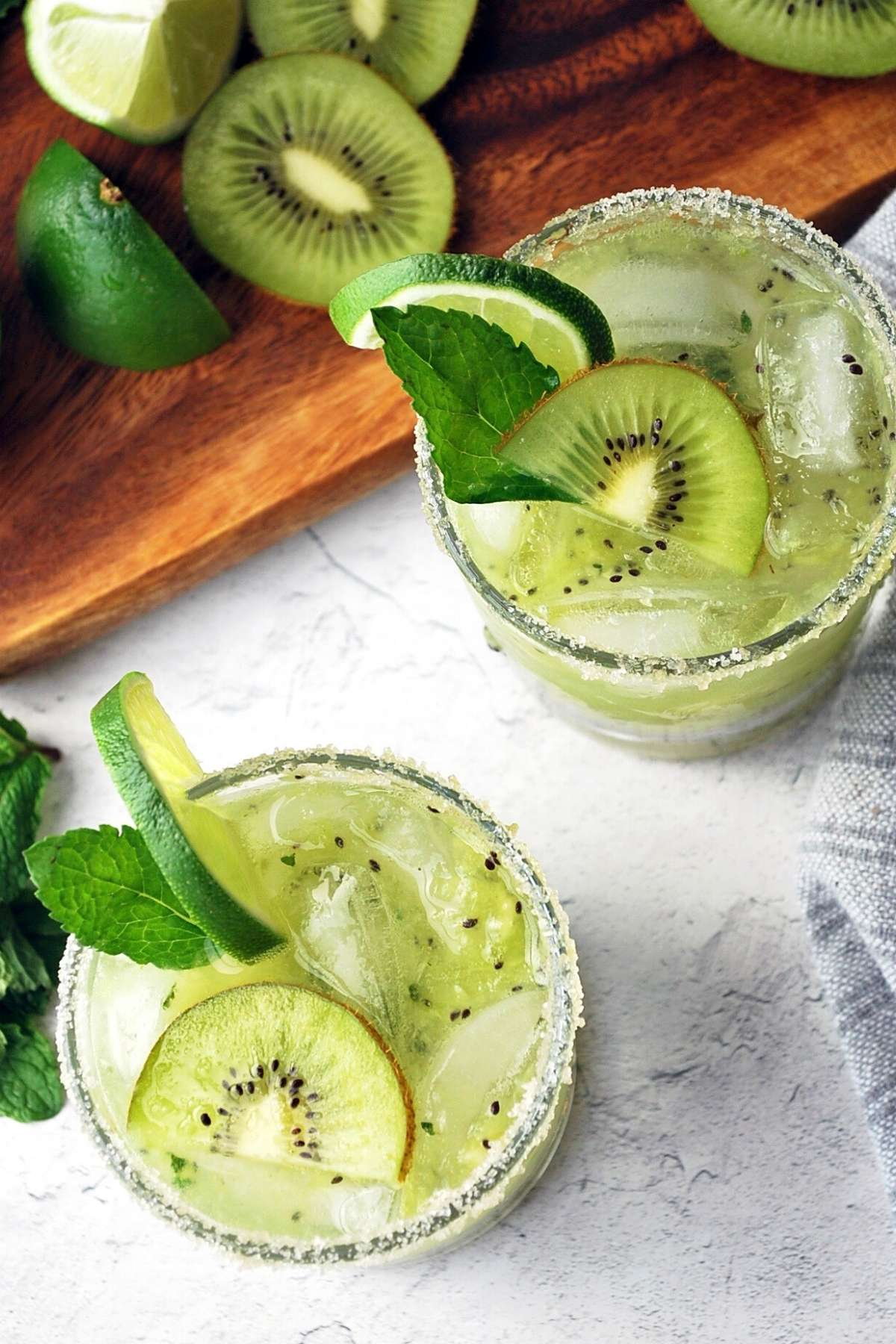 overhead shot of kiwi mojitos garnished with lime, mint, and sliced kiwi