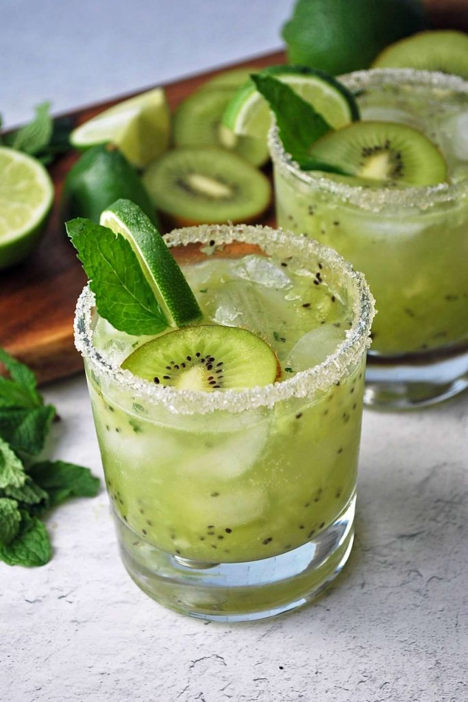 kiwi mojitos with chopped kiwi, lime, and mint on a cutting board in the background