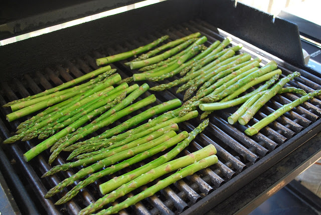 A bunch of green asparagus on a grill