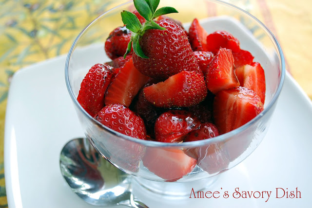 A bowl of marinated fresh strawberries with a spoon
