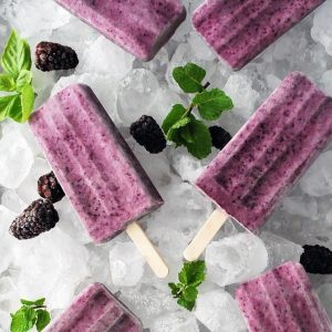 tray of popsicles with berries and mint
