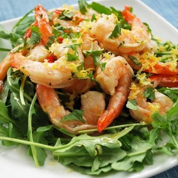 close up photo of marinated shrimp on a bed of greens with fresh herbs on top