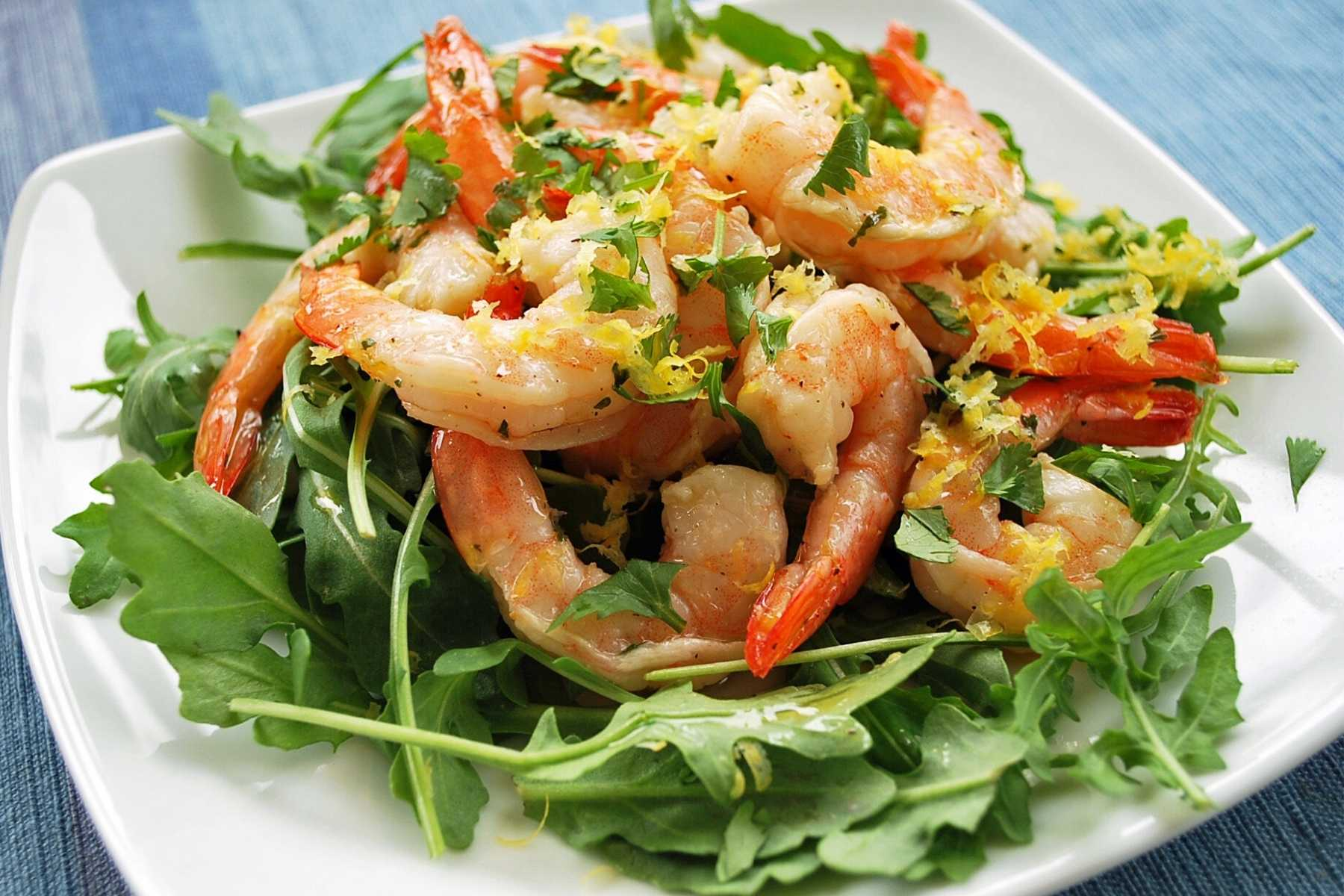 plate of shrimp over greens with fresh chopped herbs and lemon zest on top