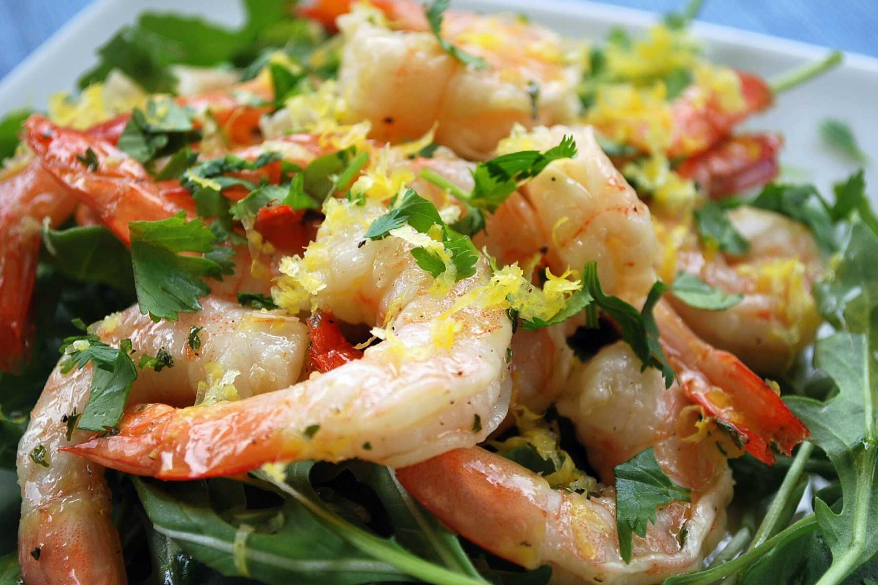 close up of marinated shrimp on a plate with greens and fresh herbs