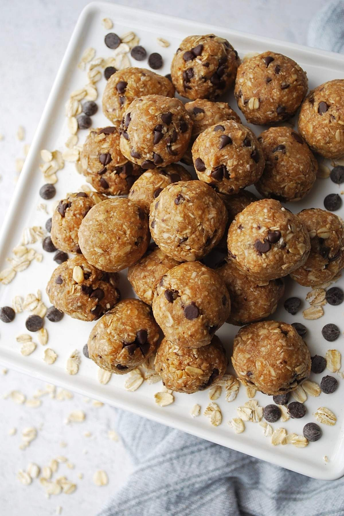 overhead photo of bliss balls with chocolate chips and oats on a platter with a napkin underneath