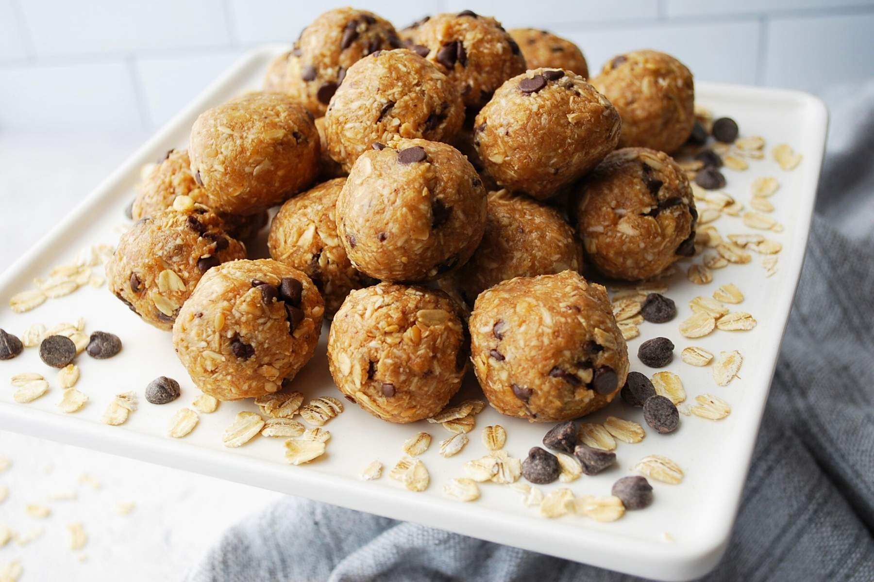 close up of bliss balls on a white platter surrounded by chocolate chips and dry oats