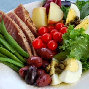 close up of sliced tuna, green beans, boiled eggs, olives, sliced potatoes, greens and capers in a bowl