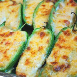 jalapeno peppers stuffed with melted cheese on a pan