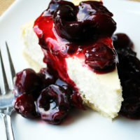A piece of Lemon Cheesecake topped with cherry sauce on a plate with a fork