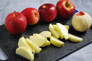 peeled and sliced apples on a cutting board with whole apples in background