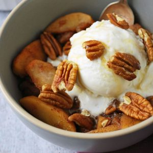 cinnamon apples in a grey bowl with ice cream and a spoon