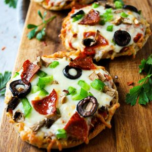 2 open-faced English muffin pizzas loaded with toppings on a serving board