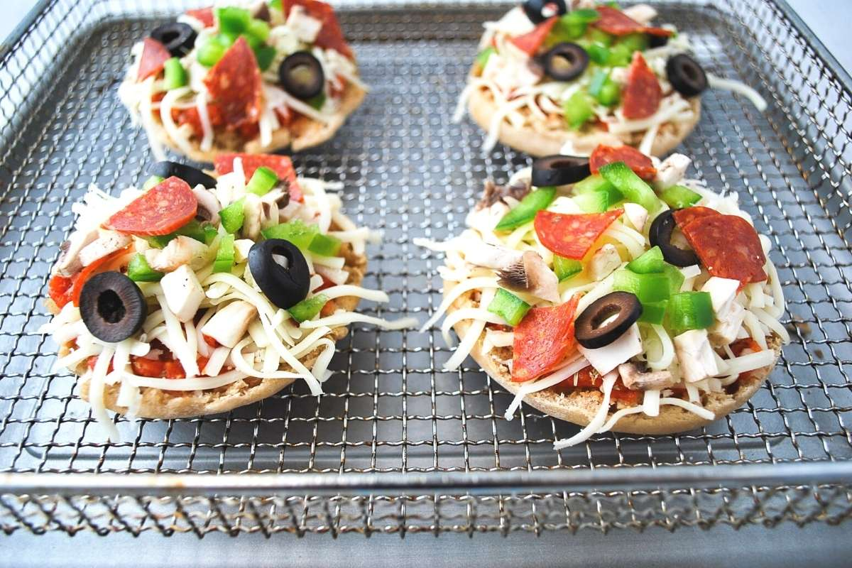 English muffins topped with toppings on a air fryer pan ready to cook