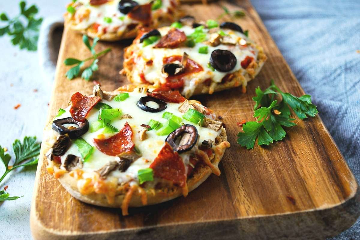 close up of cooked supreme English muffin pizzas on a wood cutting board