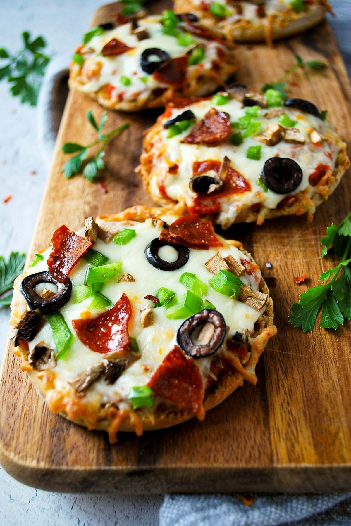Supreme air fryer english muffin pizzas on a cutting board with fresh herbs