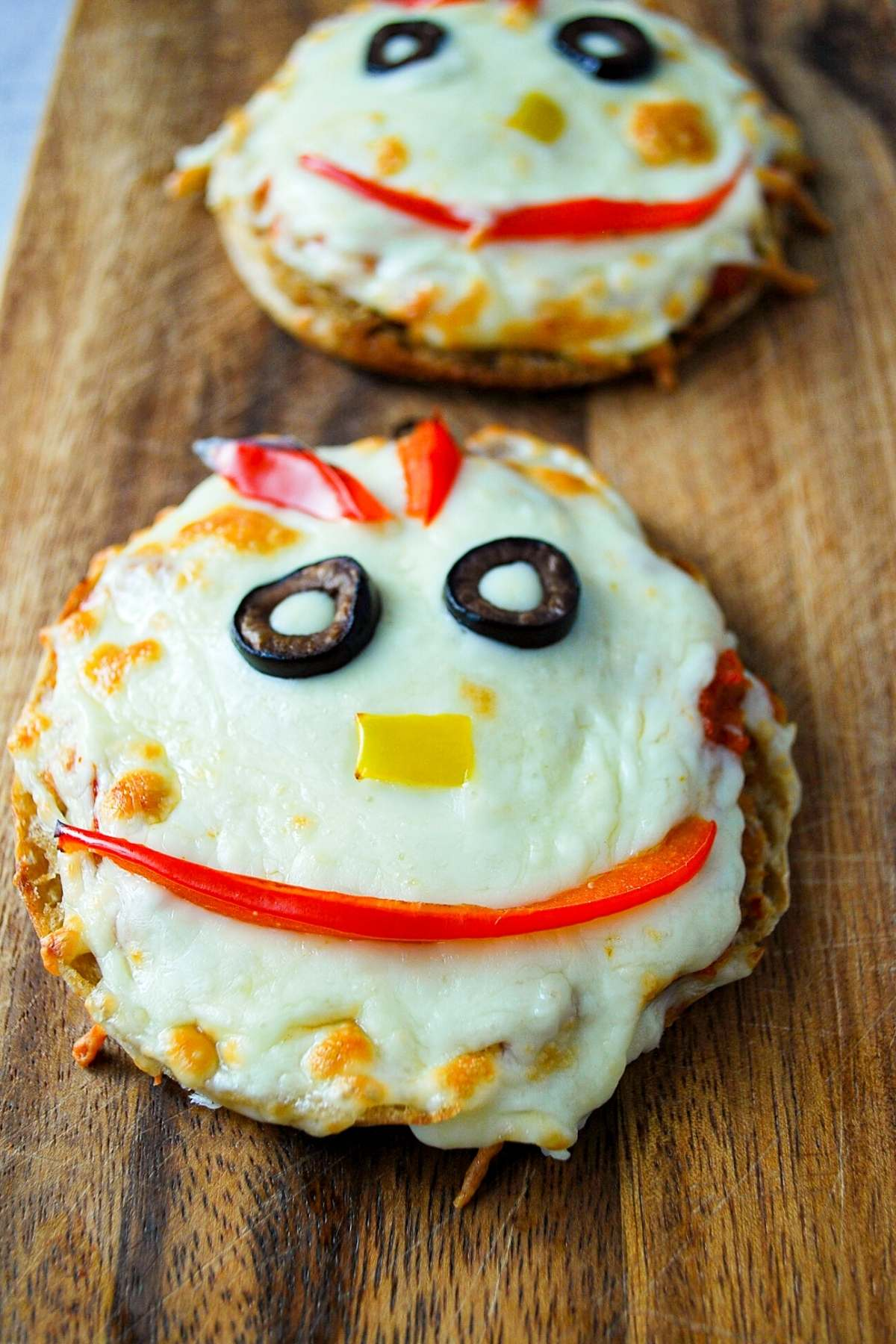monster face english muffin pizzas on a cutting board