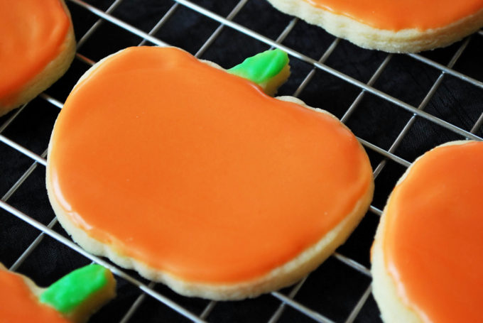 frosted sugar cookie decorated like a pumpkin