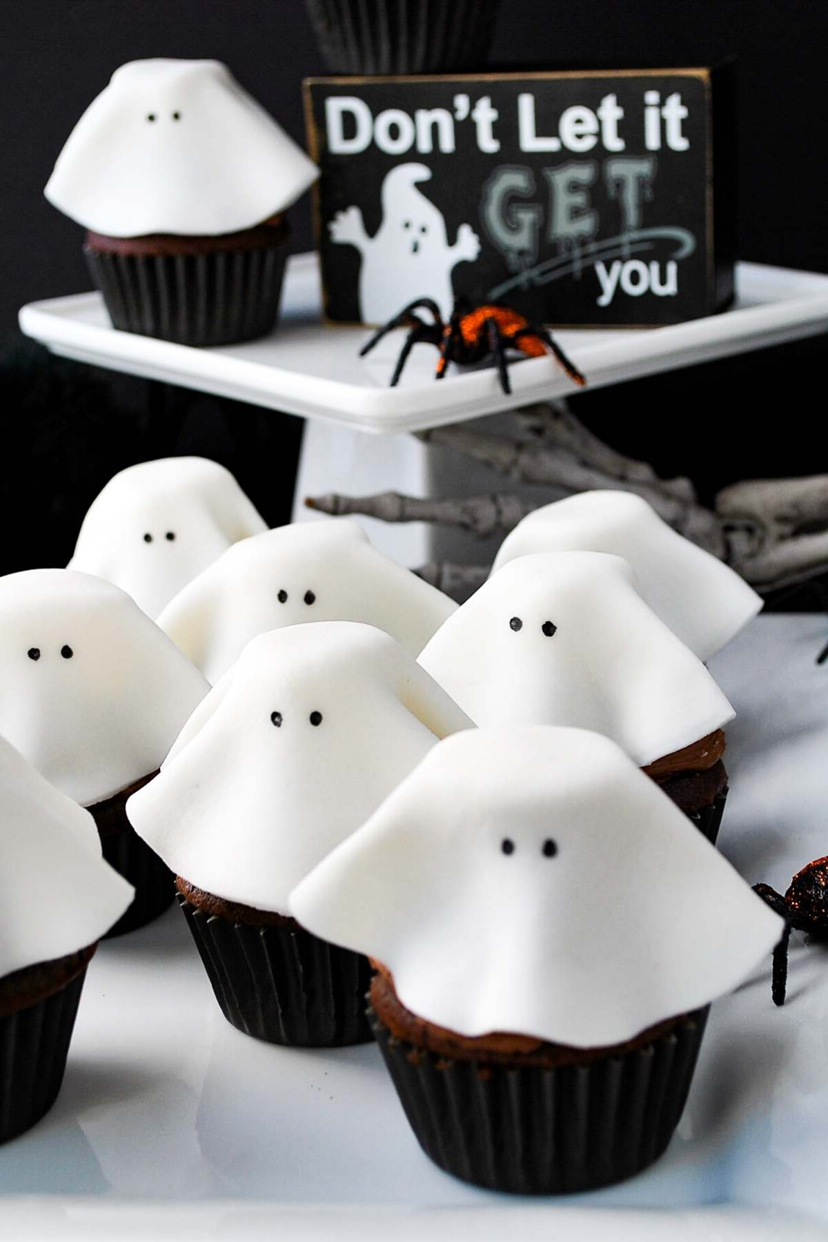 """ghost cupcakes on a serving tray with a """"don't let it get you"""" sign in the background"""