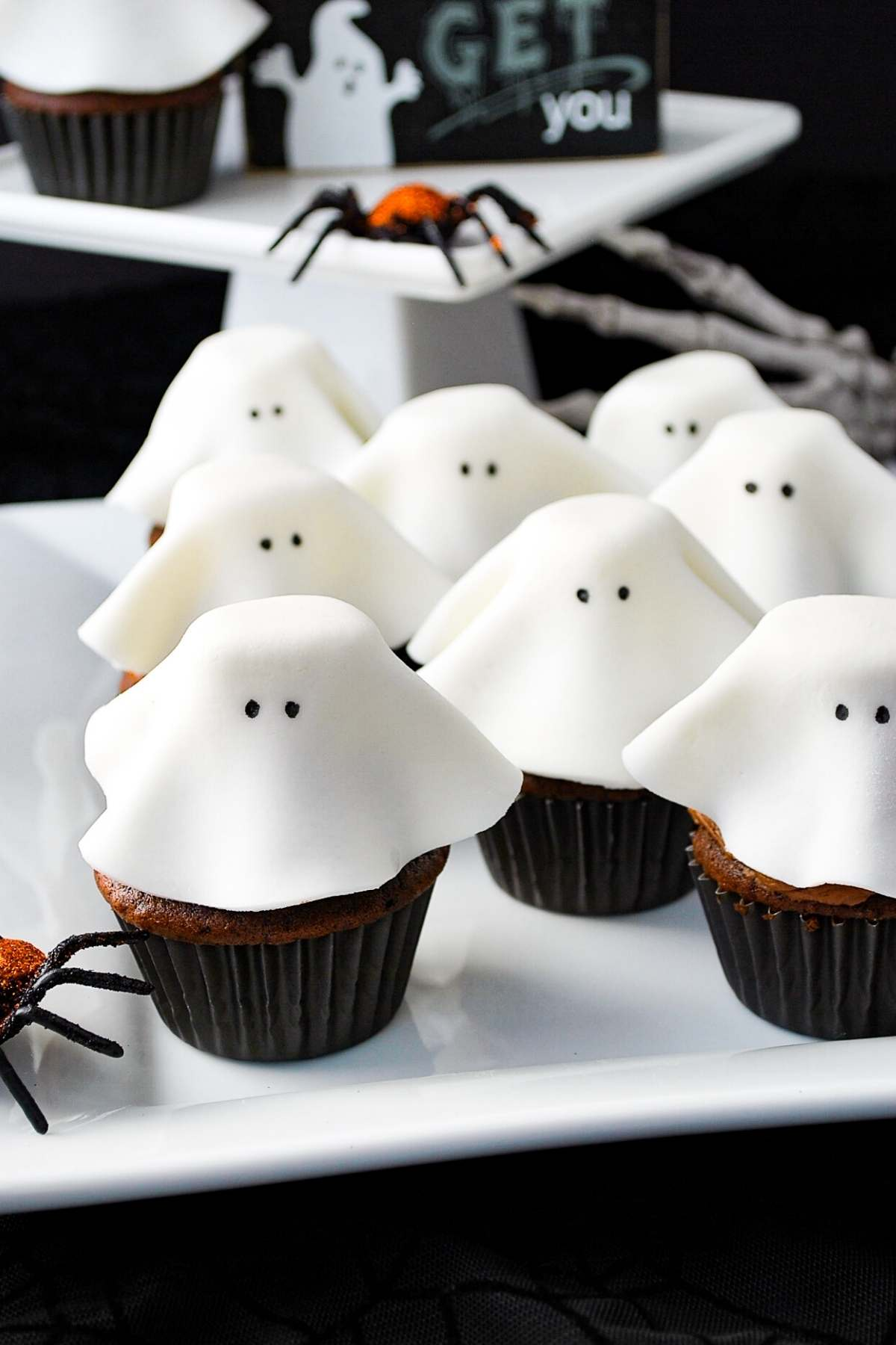 fondant ghost cupcakes on a white platter with plastic spiders