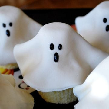 vanilla cupcakes topped with fondant shaped as a ghost with black icing eyes and mouth on a platter