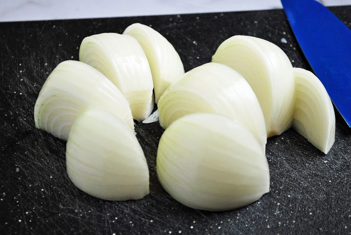 onion sliced into wedges on black cutting board