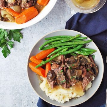 plate of beef roast with green beans and carrots and a martini with olives