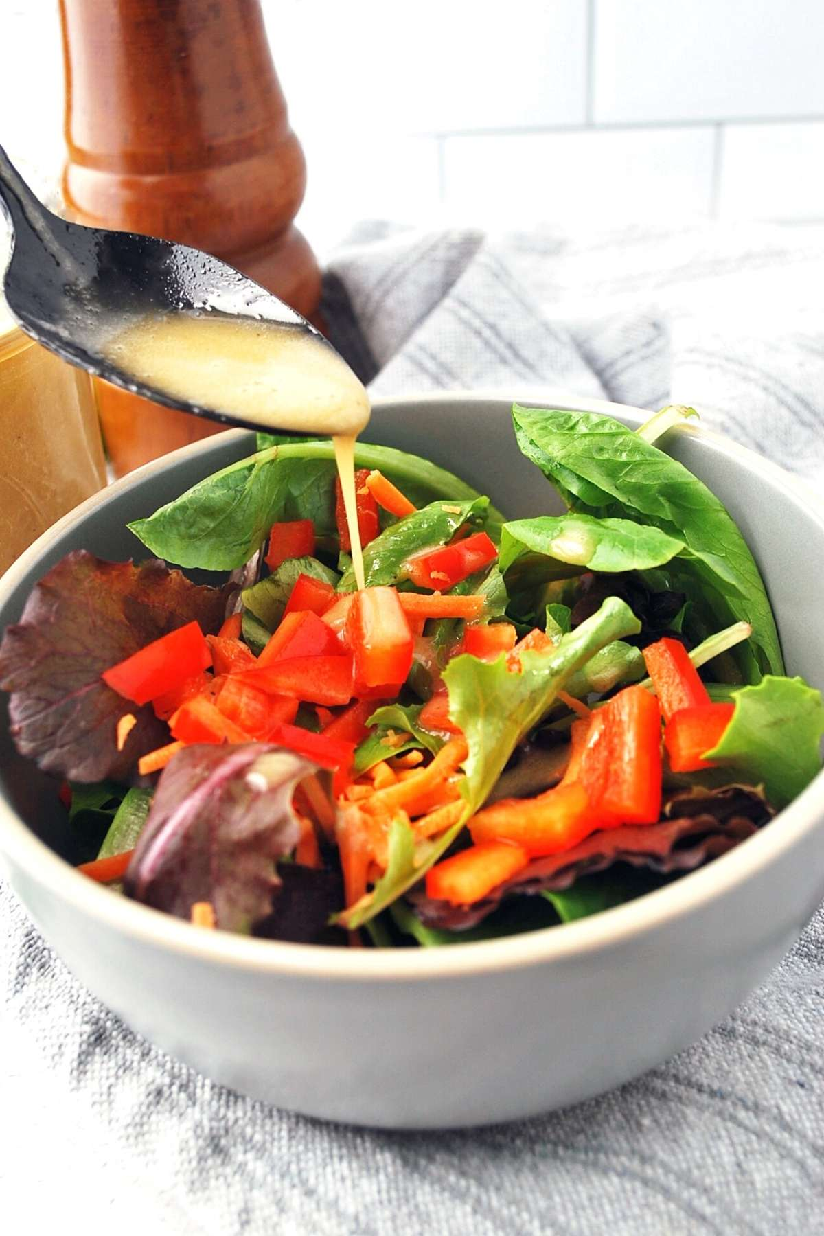 drizzling honey mustard vinaigrette onto a salad with a spoon