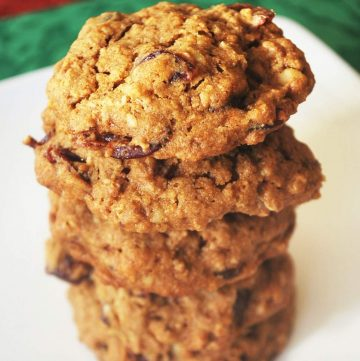stack of oatmeal cookies on a white plate on top of a green napkin