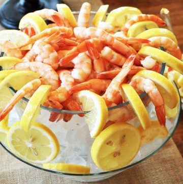 glass bowl filled with ice and lemon slices with shrimp and lemon wedges on top