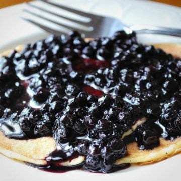 pancake topped with wild blueberry compote on a plate with a fork