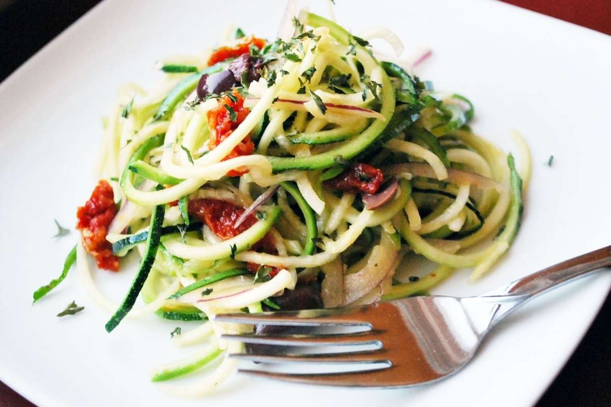 spiralized summer zucchini salad on a plate with a fork