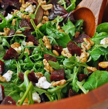 close up photo of a bowl of salad with beets, cheese, nuts, and dressing